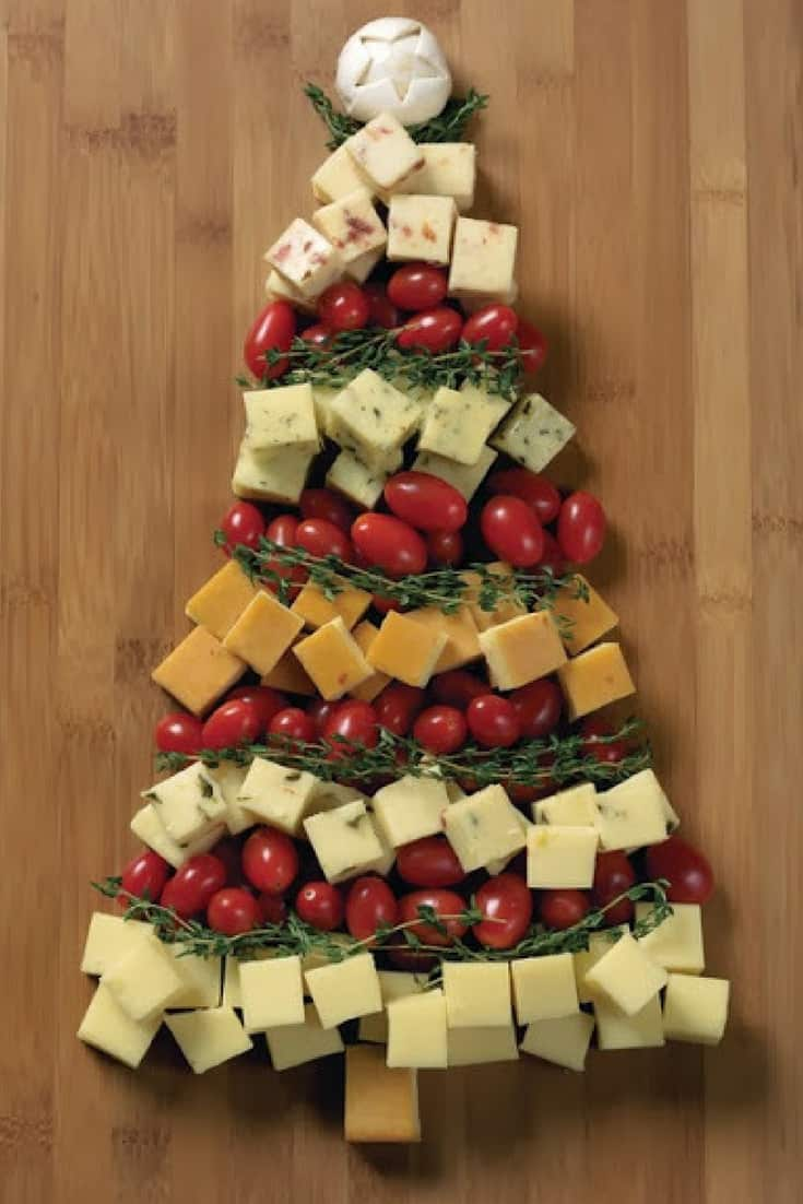 Cheese and tomatoes tree arranged on cutting board