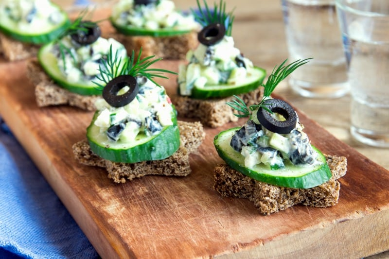 Mini sandwiches with cucumber, olives and fish salad on rustic wooden board